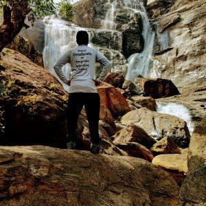 Guy Standing near Waterfall - Proud Graduate T-shirt